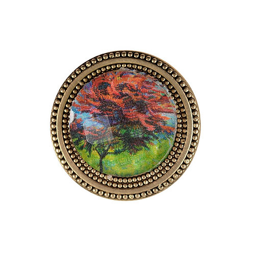 golden magnetic pin with floral imagery in red and green under a faceted crystal
