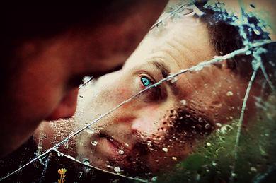 Homem atrás do vidro quebrado