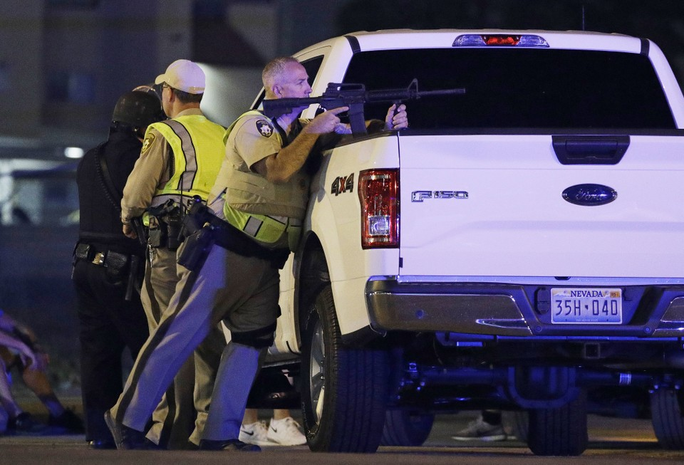 A police officer takes cover behind a truck at the scene of a shooting near the Mandalay Bay resort and casino on the Las Vegas Strip, Sunday, Oct. 1, 2017, in Las Vegas. Multiple victims were being transported to hospitals after a shooting late Sunday at a music festival on the Las Vegas Strip. (AP Photo/John Locher)