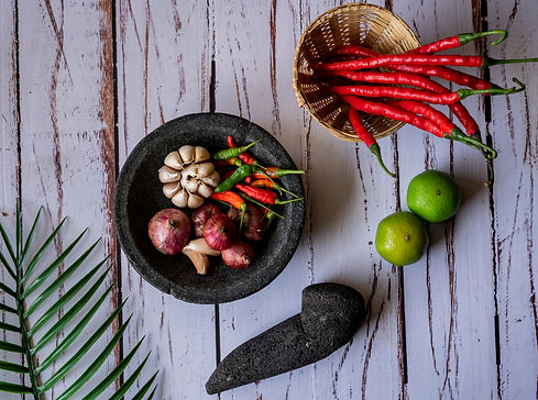 Indonesian traditional making of sambal (chili sauce) with mortar and pestle made form sto