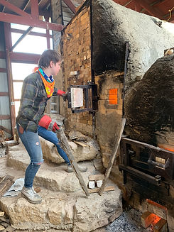 Tabitha Link stoking the wood kiln.