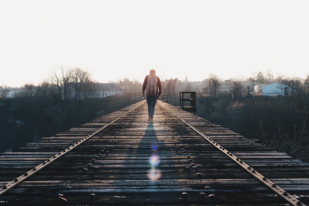 A man walking along on a train track; an introvert's dilemma