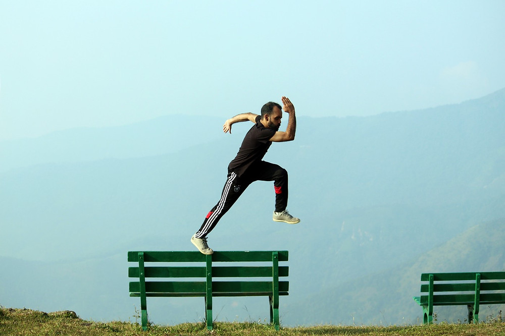 A determined man jumps off the bench into the sky