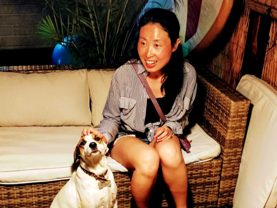 Ling (Yoga teacher) smiling, sitting on a wooden chair with a cute dog in Peru.