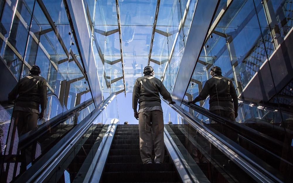 A man standing on an upwards escalator