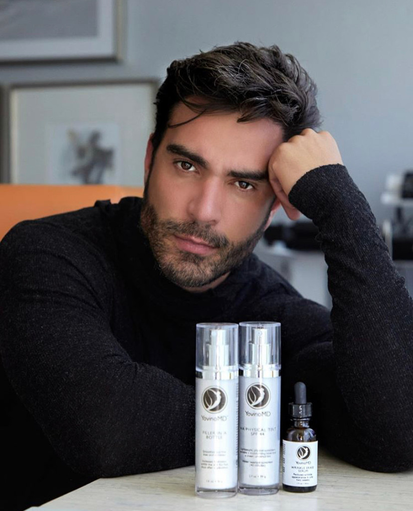 Rodiney Santiago poses with YovinoMD Filler in a Bottle, Wrinkle Erase Serum, and HA Physical Defense sunscreen.