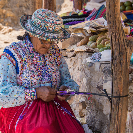 A woman weaving at her stall