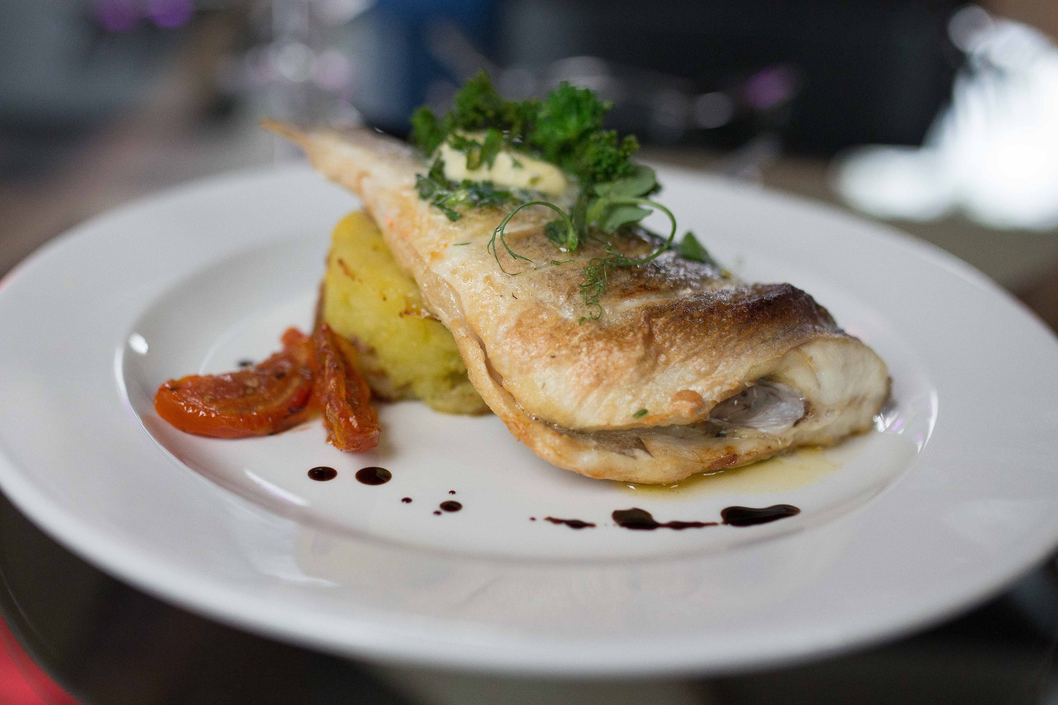 Oven-baked whole red gurnard served with garlic and parsley crushed potatoes and lemon butter