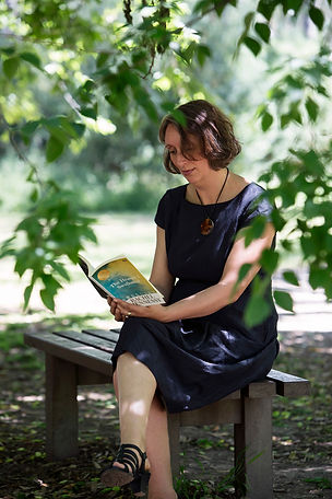 Rachel Hennessy reading her book on a bench