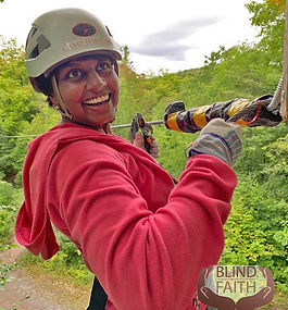 Jen Ferris with hard hat and gloves holding to a zipline type wire.