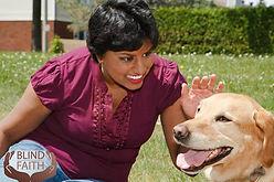 Jen Ferrs pets smiling dog on grass