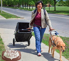 Jen Ferris walks with guide dog while pullng luggage down a neatly kept sidewalk