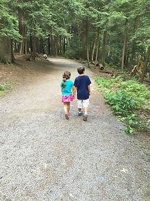 two children walking down a path