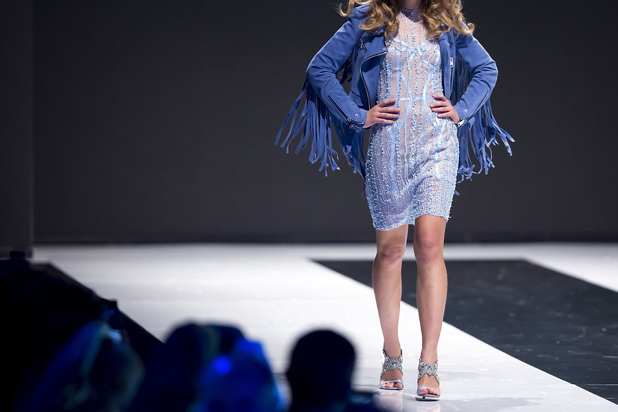 Female model walks the runway in blue dr