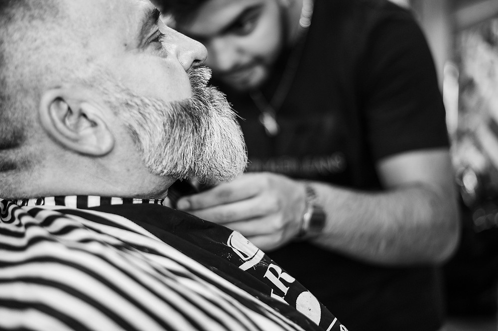 An older man, has his beard cut from the side!