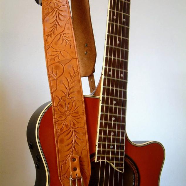 Gitarre auf Gitarrenständer und mit Gitarrengurt