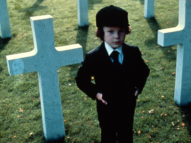 Child in black suit standing in cemetery next to cross-shaped headstone.