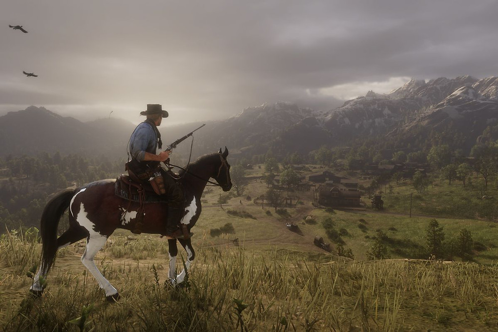 A Western outlaw circa 1899 riding a horse with rifle drawn, looking down on a small town secluded in the shadow of fog-covered mountains.