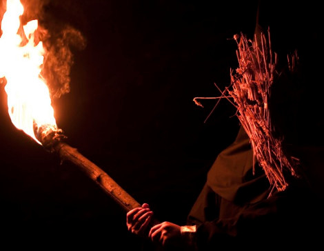 Person in straw mask holding a flaming torch at night.
