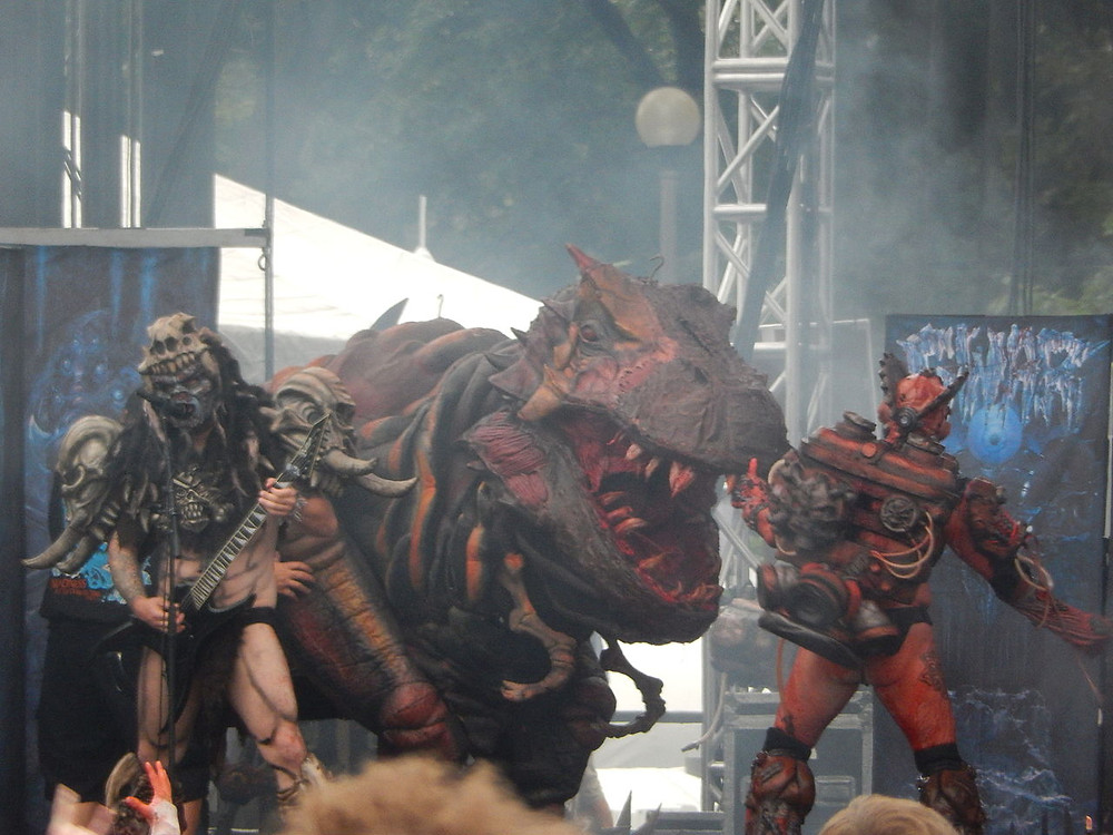 The band GWAR on stage dressed in elaborate monster costumes with a dinosaur in the background