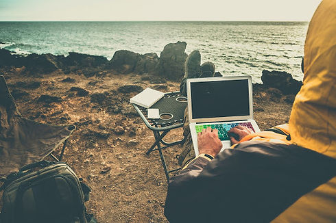 Digital nomad in yellow raincoat with laptop sitting at the seashore.