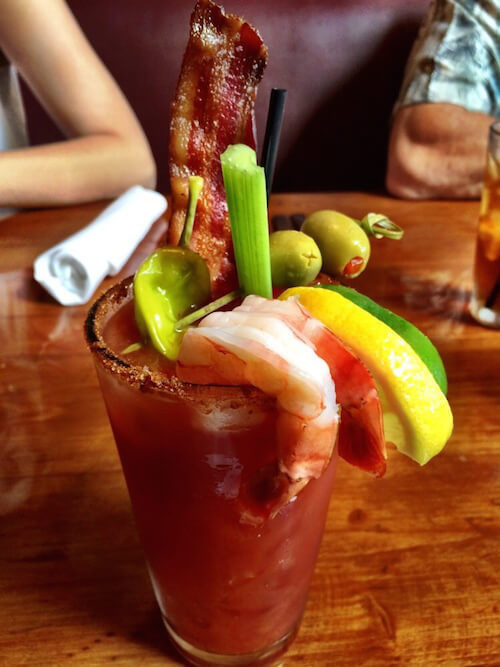 Appetizing Bloody Mary finished with bacon shrimp and pepper slices