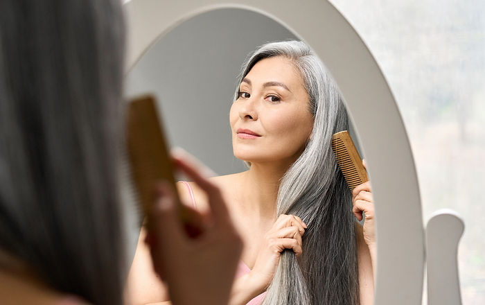 Senior attractive middle 50 years aged asian woman with gray hair looking at mirror reflec