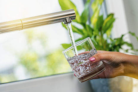 woman hand holds a glass to Filing it wi