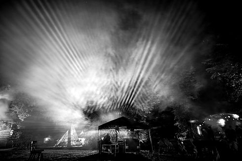 Lichtstrahlen die durch Nebel scheinen. Lichtkunst auf einem Klostergut. Beleuchtung auf einem Lichterfest.