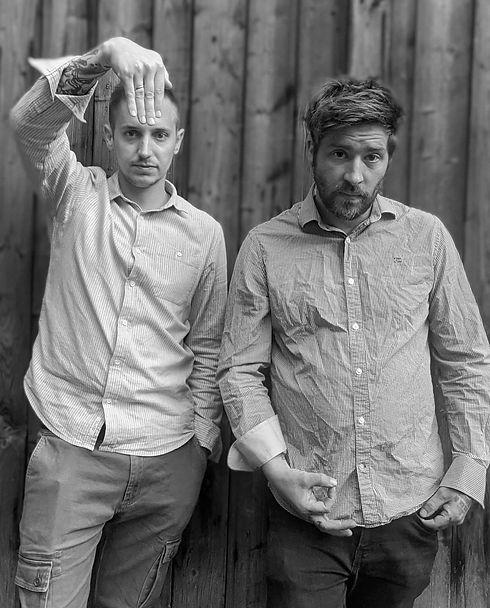 Julian und Buddy, die beiden Lichtkünstler, vor einer Holzwand.