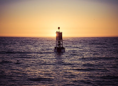 A sea buoy with the sun setting in the background