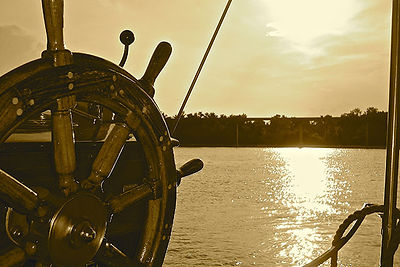 photo of a ship's wheel with water in the background