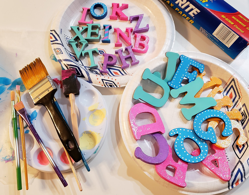 paints, paintbrushes and colorfully painted alphabet letters