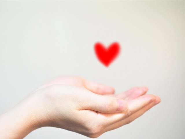 A red heart above hands