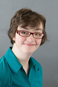 Aubrie Westmaas, a young woman with short brown hair, glasses, and a green button-down shirt smiling in a formal portrait.