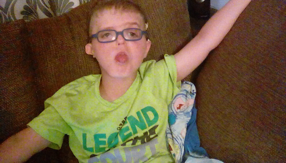 "Gannon, a third-grade boy with CHARGE syndrome, sits on a couch with his arms outstretched.  Gannon wears glasses.  His tongue is thrust out of his mouth slightly.  His t-shirt says ""Legend on the Court""."