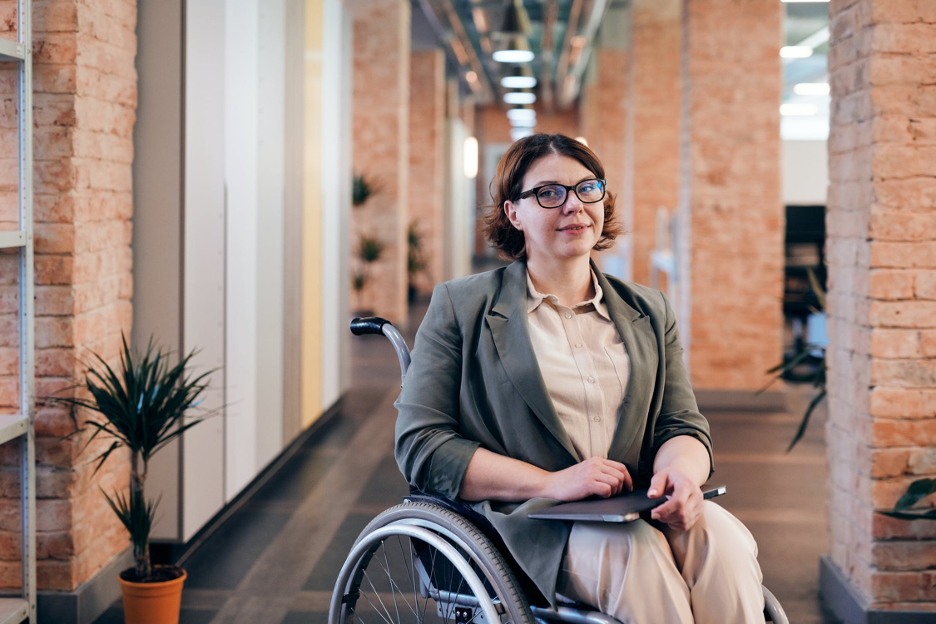 A woman with short brown hair and glasses sits in a wheelchair.  She is dressed professionally in slacks, a button-down shirt, and blazer.  She holds a laptop computer on her lap.  She is in an indoor corridor lines with brick pillars and plants.