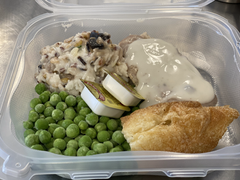 Wild rice, green peas, steak with gravy, and a crossiant roll