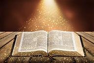 old open bible book on abstract bokeh ba