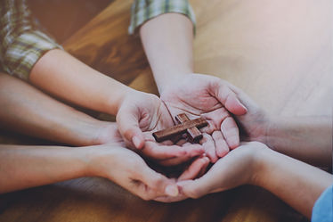Three people hands holding small wooden