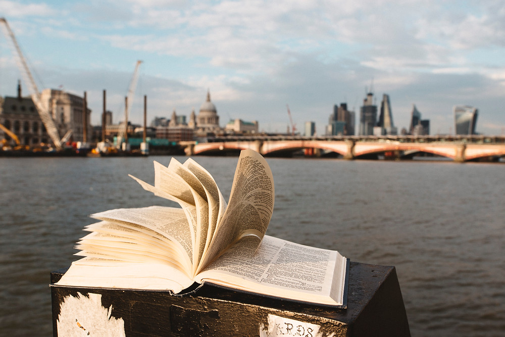 Open book with pages flapping in front of the Thame. Southwark Bridge in far distance