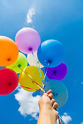 Hand holding multicolored balloons with