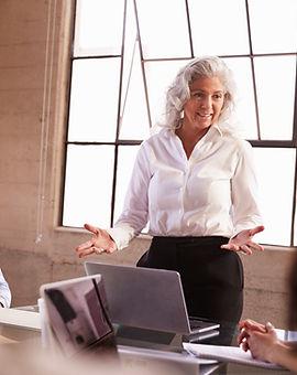 senior-businesswoman-addressing-colleagu