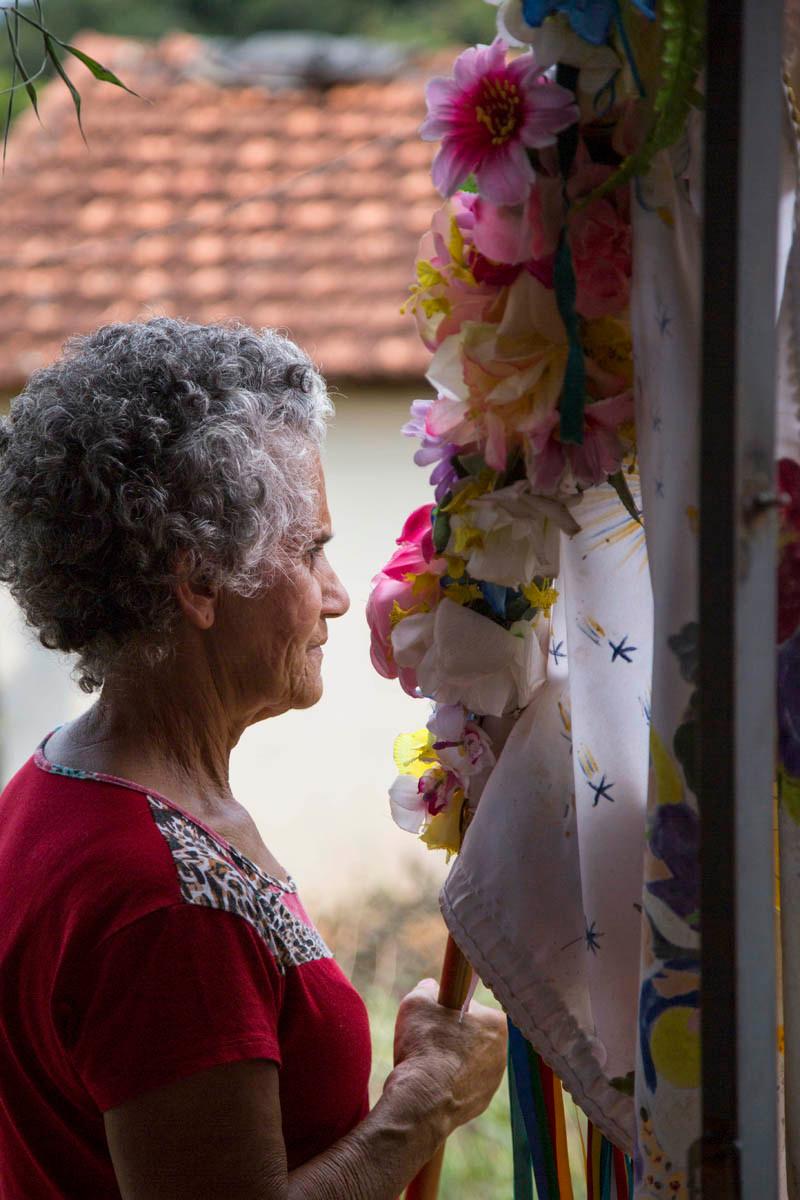 Dona da casa visitada pela Folia de Reis segura a bandeira e recebe os integrantes do grupo na porta da sua casa