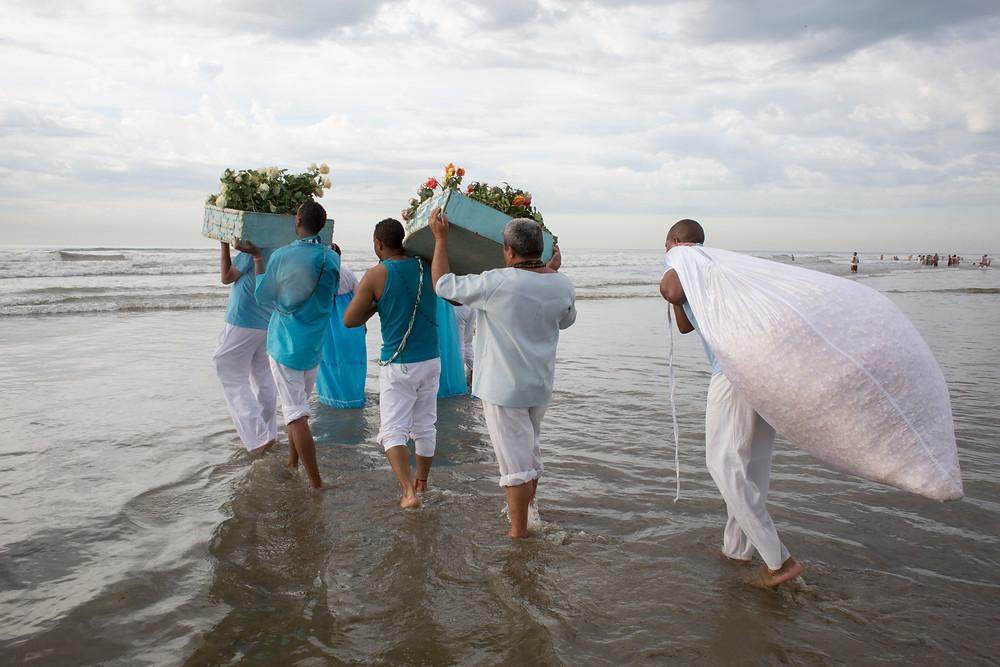 Grupo levando oferendas para Iemanjá na Praia Grande, litoral de São Paulo