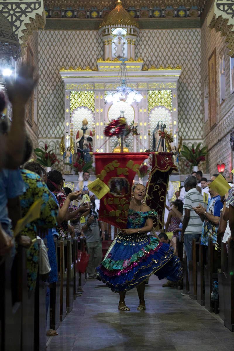 Integrante de Terno de Reis dança dentro da Igreja da Lapinha em Salvador como parte das celebrações do Dia de Reis