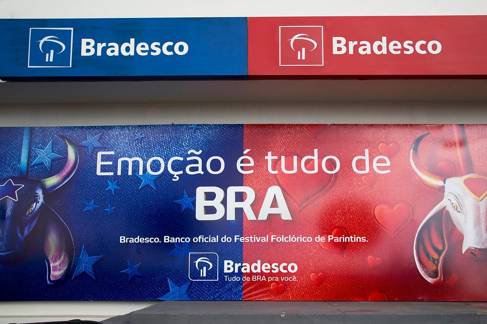 Logo do Bradesco em versões azul e vermelha, especial de Parintins