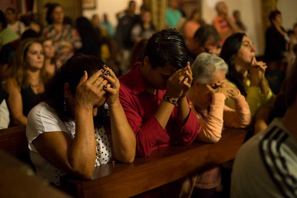 Fiéis católicos oram durante a missa de Quaresma em Tiradentes, Minhas Gerais