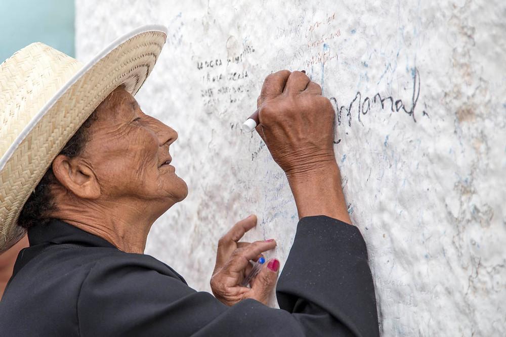 Romeira de Padre Cícero escreve seu nome na base da estátua na Colina do Horto em Juazeiro do Norte, durante a Romaria de Finados