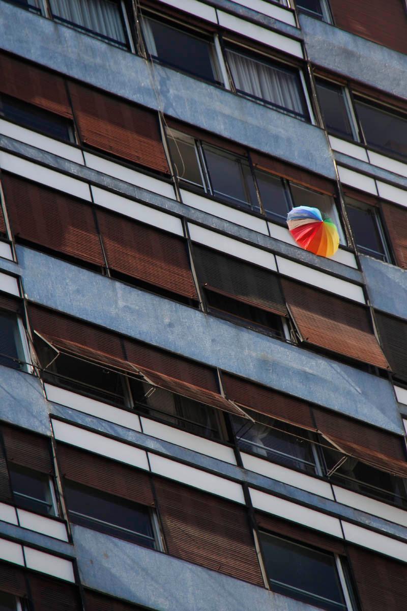 Bandeira com arco iris LGBT pendurada na janela de um edifício na Avenida Paulista